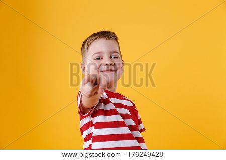 Portrait of a smiling little boy pointing finger at camera isolated over orange background