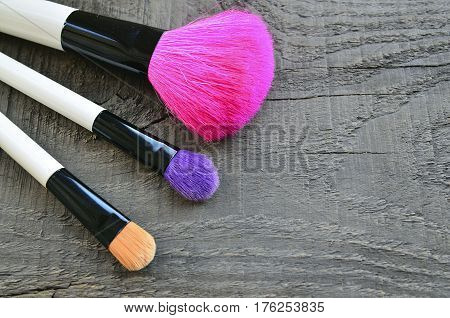 Makeup brushes on old wooden background with copy space. Colorful make-up brushes set for makeup. Fashion cosmetic makeup or woman beauty accessories concept. Selective focus.