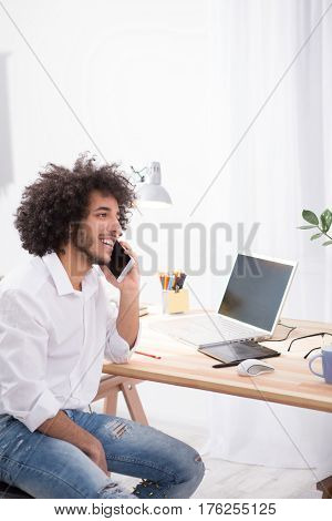 Freelance concept. Handsome man working on laptop computer at home alone. Happy hipster freelance man looking away and talking over mobile or smart phone.