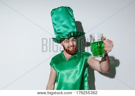 Happy bearded man in green costume holding cup of green beer and looking at camera over gray background