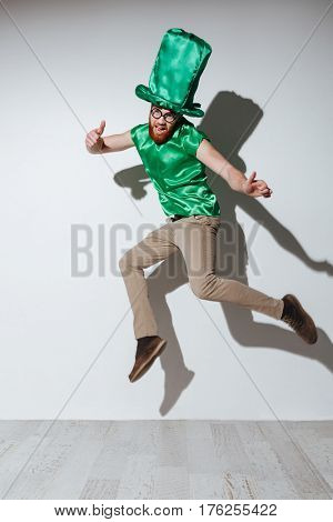 Vertical image of happy man in st.patriks costume which jumping with open mouth and showing thumb up while looking at camera. Isolated gray background
