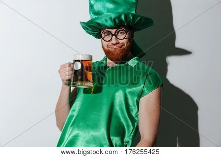 Drunk man in st.patriks costume and eyeglasses which holding cup of beer and looking at camera. Isolated gray background