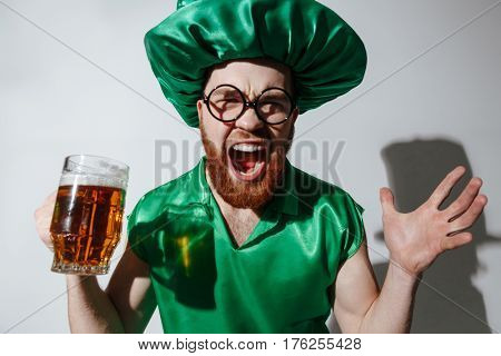 Screaming man in st.patriks costume and eyeglases which holding cup of beer in hand over gray background