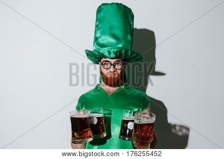 Displeased man in st.patriks costume and eyeglasses which holding many cups of beer and looking at camera over gray background