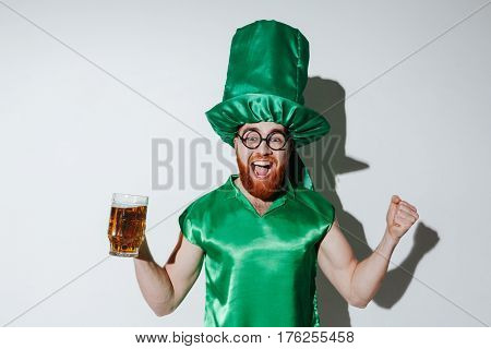 Portrait of happy bearded man in st.patriks costume and eyeglasses which holding cup of beer and looking at camera over gray background