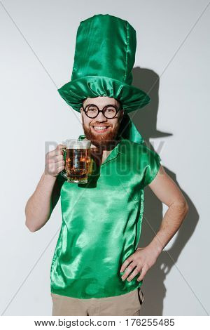 Vertical image of Smiling man in st.patriks costume and eyeglasses which holding cup of beer and looking at camera over gray background