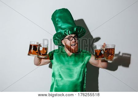 Happy bearded man in st.patriks costume and eyeglasses which holding many cups of beer and looking at camera over gray background