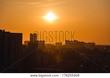 City in sunset time, Silhouettes of houses in the evening haze and the rays of the setting sun, evening cityscape