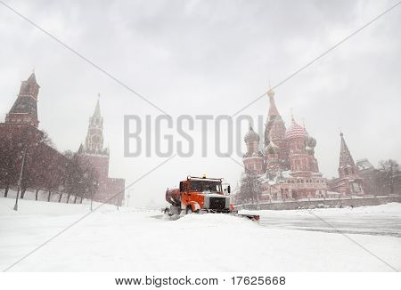 Snow-remover truck clean the road near Red Square, St Basil Temple and Spasskaya Tower of Kremlin in Moscow, Russia at wintertime during snowfall