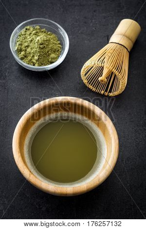 Matcha green tea in a bowl and bamboo whisk on black slate.