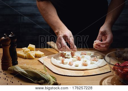 Chef cooking pizza, putting topping on pizza base. Low key shot, close up of hands, some ingredients around on table.