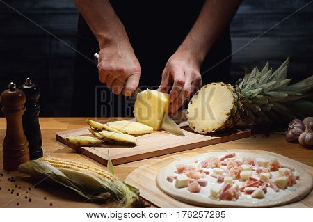 Chef cooking hawaiian pizza, cutting fresh pineapple. Low key shot, close up of hands, some ingredients around on table.