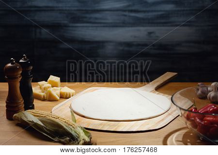 Cooking pizza background, dough base on board. Low key shot; light on dough; some ingredients around on table. Copy space.