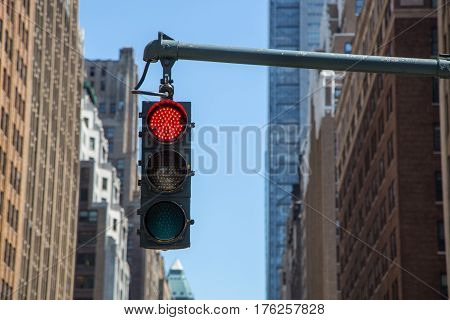 yellow traffic light on the background of skyscrapers in New York. Glowing red light.
