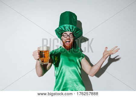 Image of happy man in st.patriks costume and eyeglasses which holding cup of beer and looking at camera with open mouth. Isolated gray background