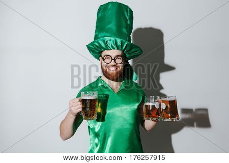 Smiling man in st.patriks costume and eyeglasses which holding cups of beer and looking at camera over gray background