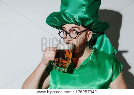 Happy man in st.patriks costume and eyeglasses which drinking beer and looking at camera over gray background