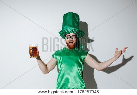 Portrait of happy man in st.patriks costume which screaming and holding cup of beer while looking at camera over gray background