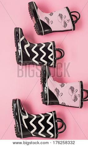 The Black, white and pink rubber boots or gardening boots on pink studio background