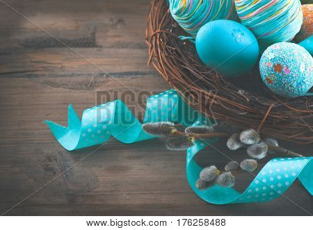 Easter colorful painted eggs on wooden table top background. Beautiful colourful eggs with spring flowers and blue satin ribbon over wood brown backdrop, art border design. Vintage style