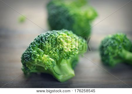 Broccoli. Closeup of fresh green Broccoli Bunch over wooden background. Healthy food, diet, dieting concept. Vegan food close up, selective focus
