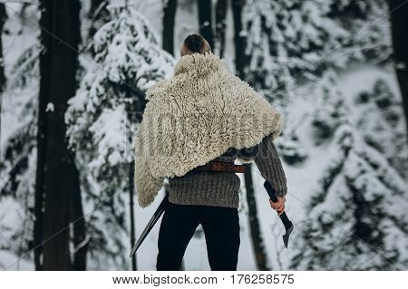 Strong Viking Warrior With Mohawk Haircut And Wolf Pelt Armor Holding Axe And Walking In Winter Wood