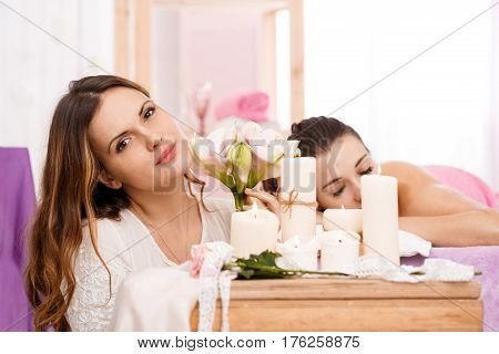 Messeur behind lighted candles, holding flowers with relaxing young woman on background at spa salon