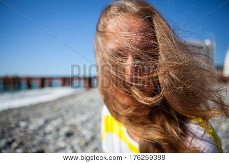 Young pretty girl in summer sunny day on the street near the sea. A strong wind disheveled the hairstyle