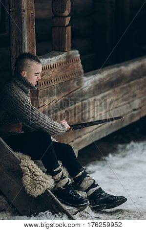 Strong Viking Warrior Sharpening His Sword While Sitting Near Ancient Wooden Castle, Scandinavian Kn