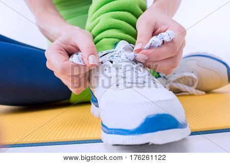 close up view of woman tying shoe laces on white