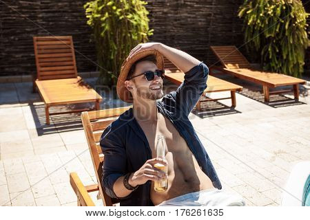 Young handsome man in sunglasses and hat drinking beer, sitting on chaise. Copy space.