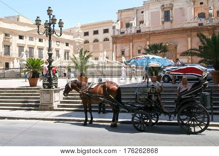 Horse Carriages On Piazza Pretoria With Magnificent Fountain