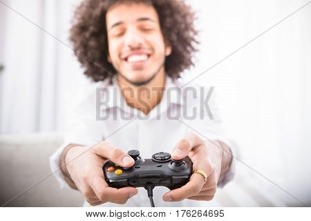 Computer games concept. Closeup of young hipster man holding joystick while playing computer games in front of laptop computer or television.