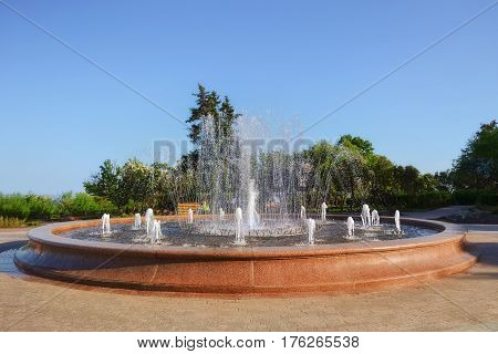 Granite fountain in a Park in Ulyanovsk, people in the distance.