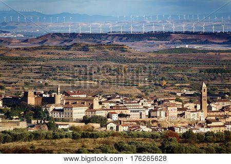 Long shot of old village, plain terrain and modern wind turbines