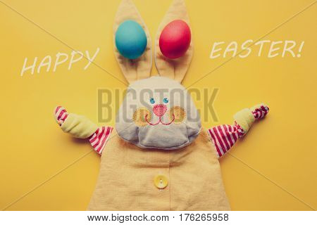 Easter Decorations From A Handmade Toy Rabbit And Colorful Eggs On An Orange Background. With Retro