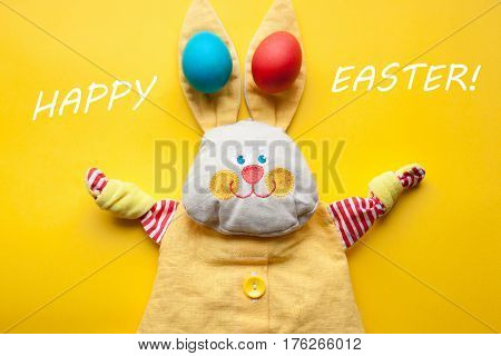 Easter Decorations From A Handmade Toy Rabbit And Colorful Eggs On An Orange Background. With The Wo