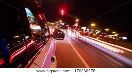 Detail of car driving in city at night, blur motion