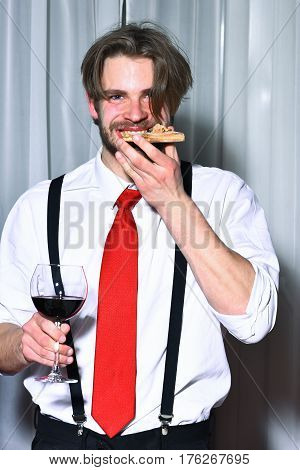 Happy bearded man or hipster with beard wearing white shirt red tie and black suit pants with suspenders eating tasty pizza and drinking wine in glass in pizzeria cafe or restaurant on white curtain