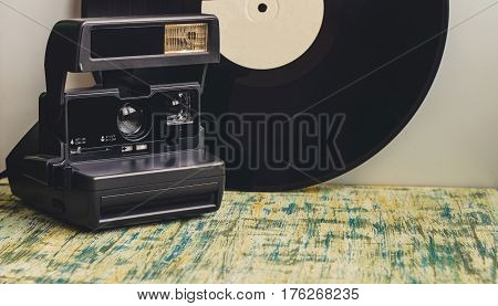 Retro Camera On The Background Of A Gramophone Record.