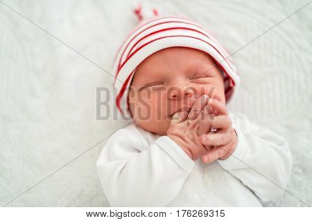 Sleeping newborn baby on back on white bed in a striped white and red cap sucks a finger . Close up