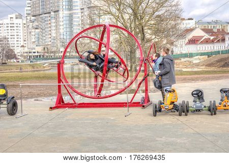 BELORUSSIA MINSK - March 11.2017: The girl is spinning in a crazy attraction on a city street