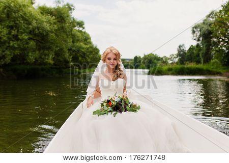 Bride portrait in a white boat at summer sundown