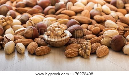 Various nuts pile on a wooden table close-up