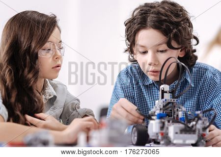 Talented science pioneers . Smart crafty involved kids sitting at school and having science lesson while demonstrating skills