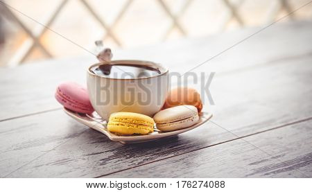 Macaroon Cookies And White Coffe Cup On Wooden Table