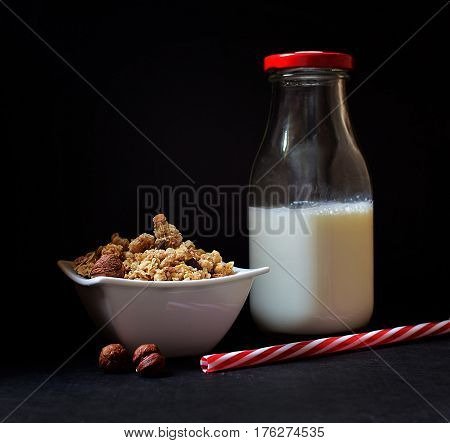 Healthy breakfast - cereal musli and milk on dark background