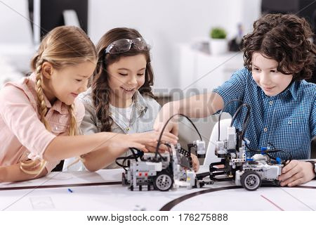 Delighted from project. Smiling upbeat optimistic children sitting at class and testing robot while working on the tech project