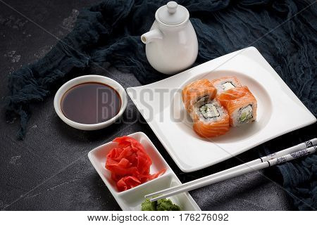 Sushi Roll On A White Plate, Decorated Like In Restaurant Over Dark Concrete Background
