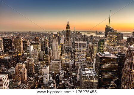 New York City. Manhattan downtown skyline with illuminated Empire State Building and skyscrapers at dusk.
